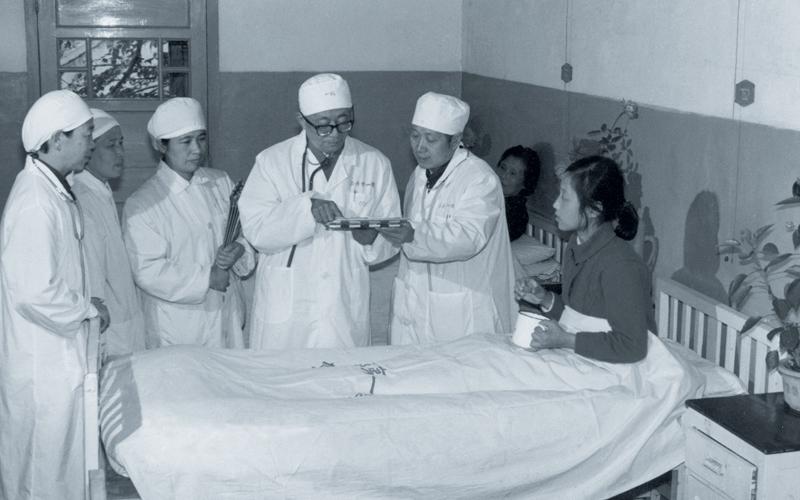五六十年代,ca888医院曾是国内重要的血防临床基地。图为国内知名血防专家、原ca888医院院长周学章同志在病房查看患者病情。